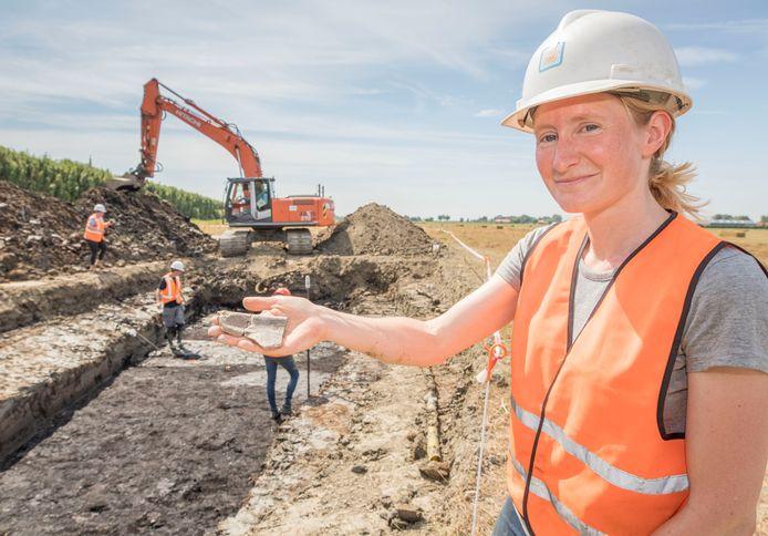 Archeologe Helle Molthof van RAAP laat potscherven zien die zijn gevonden. Achter haar de plaats van het archeologisch onderzoek in opdracht van Tennet.