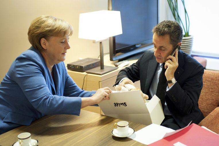 Sarkozy belt met Carla Bruni, na ontvangst van het kadootje. Beeld ap