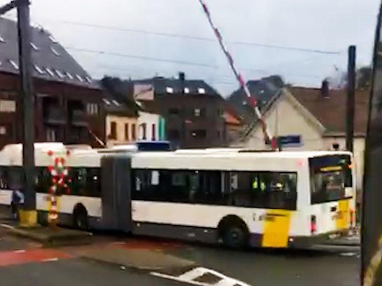 Lijnbus rijdt door rood licht aan overweg en raakt ei zo na sluitende slagboom