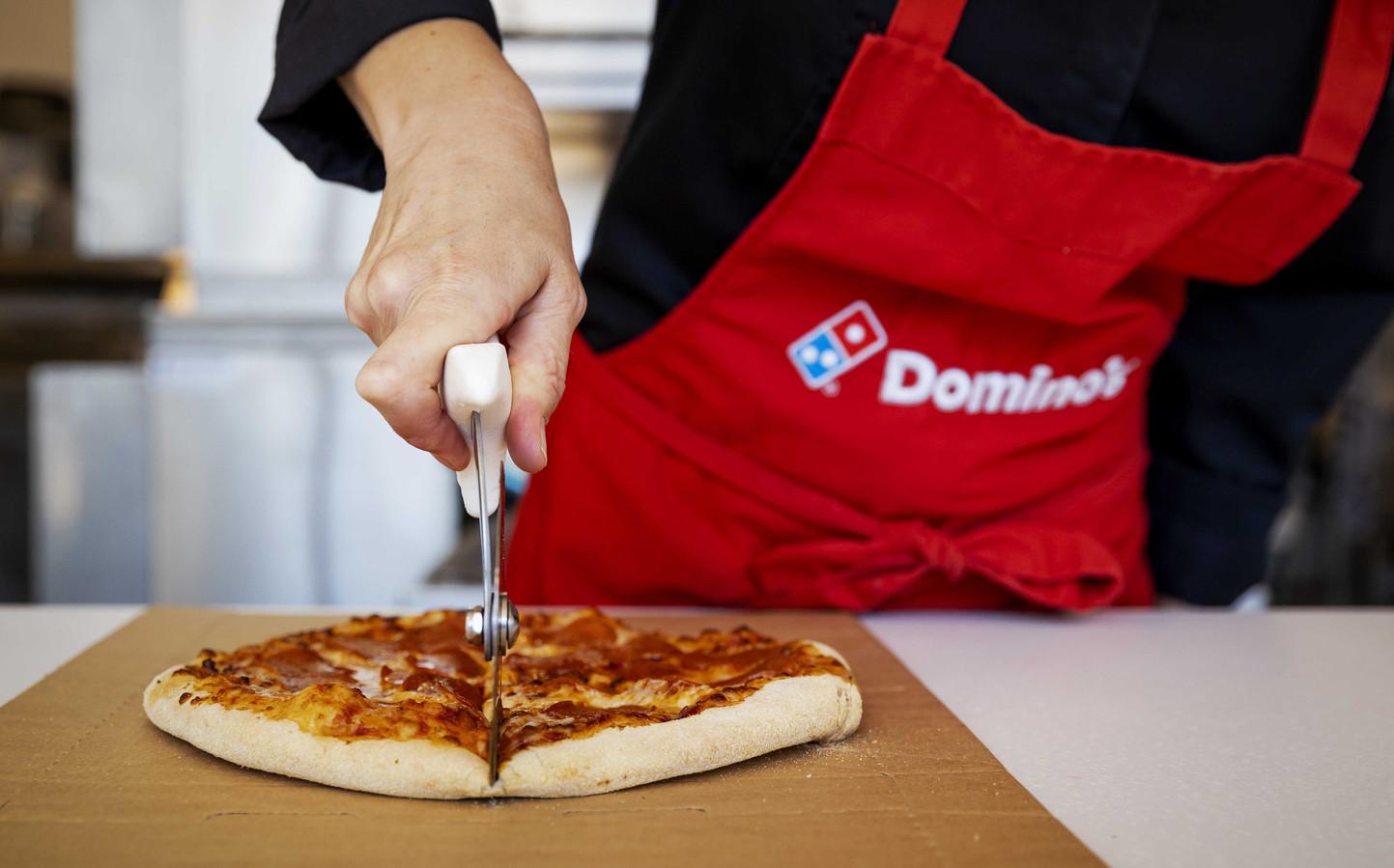Een medewerker van Domino's snijdt een pizza