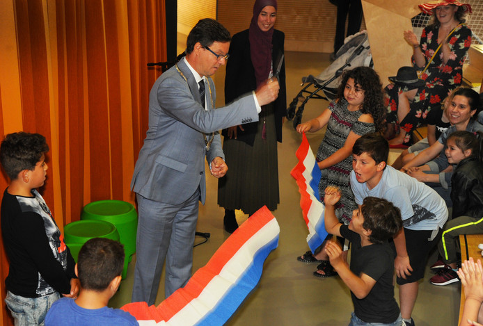 Burgemeester Bas van den Tillaar opende vandaag onder goedkeurend oog van directeur Siham Darkaoui de Vlissingse zomerschool. De burgemeester kreeg hulp van Youssef (links), die de schaar aangaf, en Umut (op de rug gezien) en Meryem, die het rood-wit-blauwe lint vasthielden .