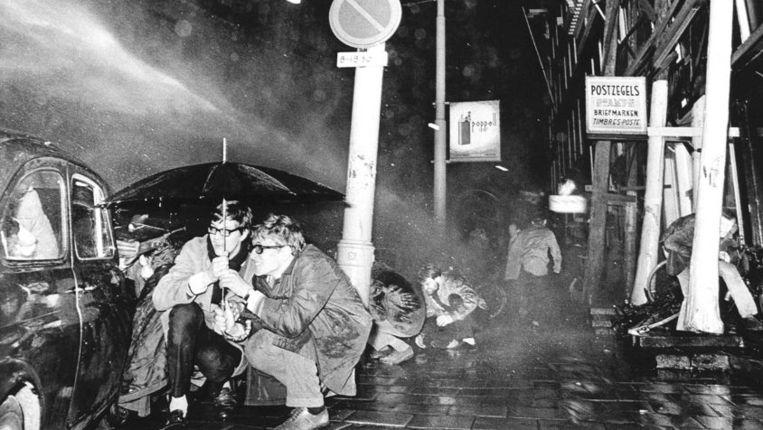 Huub Mous (rechts), de auteur van dit artikel, zoekt ten tijde van de Maagdenhuisbezetting dekking tegen een politiecharge met een waterkanon. Beeld