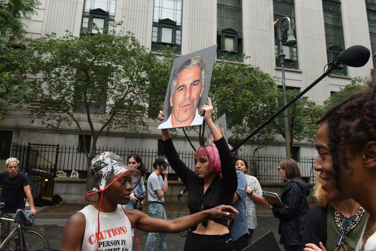 Betogers houden een foto van Jeffrey Epstein omhoog voor het gerechtsgebouw in New York. Beeld AFP