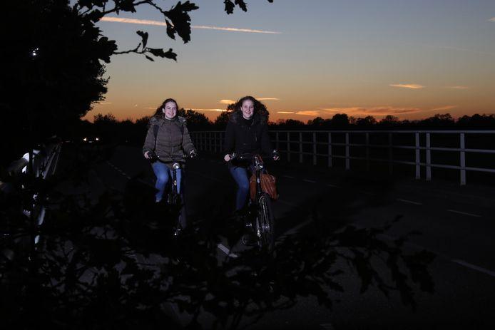 Laura Arts (l) en Kim van Neerven moeten door het donker fietsen omdat de buurtbus niet rijdt.