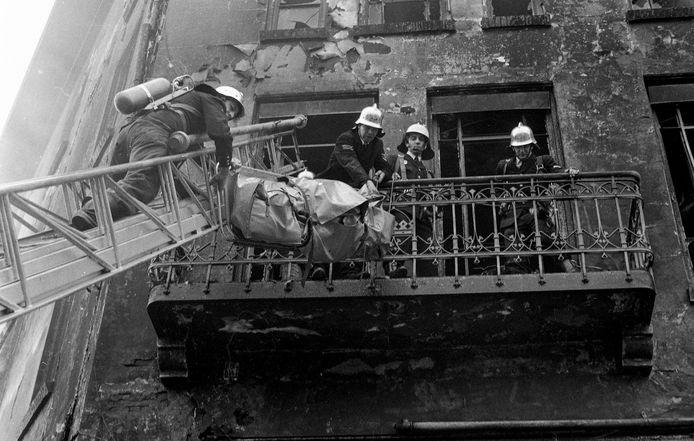Brandweerlieden halen een slachtoffer van de brand in Tsilveren Seepaerd uit het geblakerde hotel.