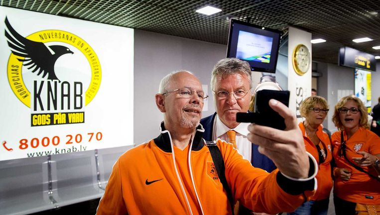 Op de luchthaven van Riga in Letland maakt een fan een selfie met bondscoach Guus Hiddink. Beeld ANP