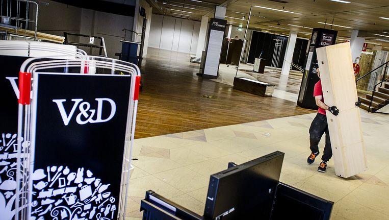 Medewerkers strippen het pand van de V&D Delft om het klaar te maken voor een nieuwe huurder. De vestiging van het failliete warenhuisconcern sloot eerder al zijn deuren voor het winkelend publiek. Beeld null