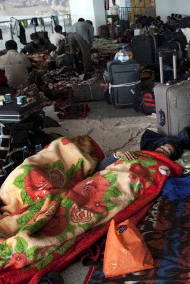 Vluchtelingen overnachten massaal in de luchthaven van Djerba. Beeld AP