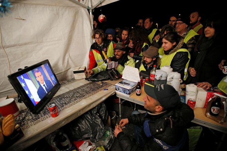 Demonstranten van de gele-hesjesbeweging kijken op een televisiescherm naar de Franse president Macron in de buurt van Marseille. Beeld REUTERS