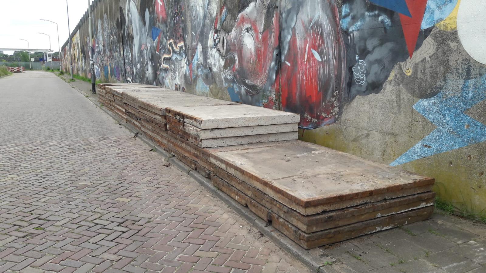 Een aantal betonplaten ligt opgestapeld langs de Markkade.
