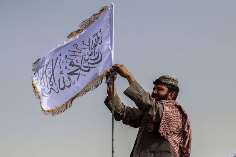 Een Talibanstrijder hijst de vlag van de Taliban. Beeld EPA