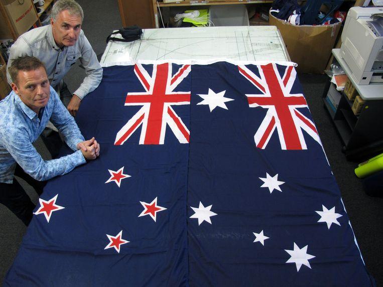 Victor Gizzi (links) en David Moginie van het bedrijf Flagmakers bij een vlag van Australië (rechts) en Nieuw-Zeeland (links). Beeld ap