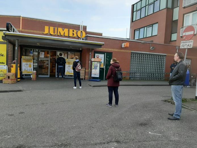 Op afstand, in de rij voor de supermarkt in Assendorp.