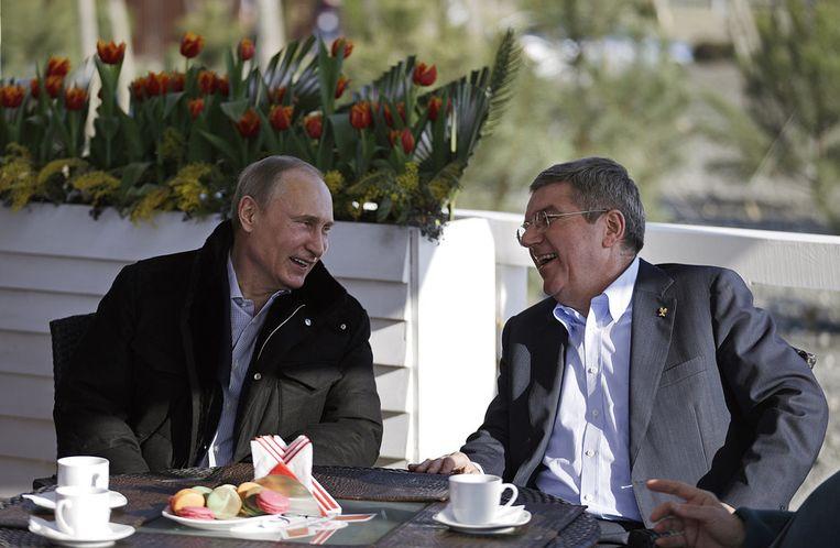 De Russische president Vladimir Poetin zit met Thomas Bach, de voorzitter van het Internationaal Olympisch Comité, op een terras langs de boulevard. Beeld AP