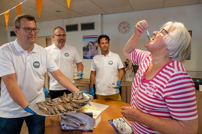 Edo koole, Ivo van der Velde, en Ewoud Verhoef brengen namens de Lionsclub Vlissingen haring bij bewoners van de Zoute Viever in Oost-Souburg. Bewoonster Ger Schipper laat het haar smaken.