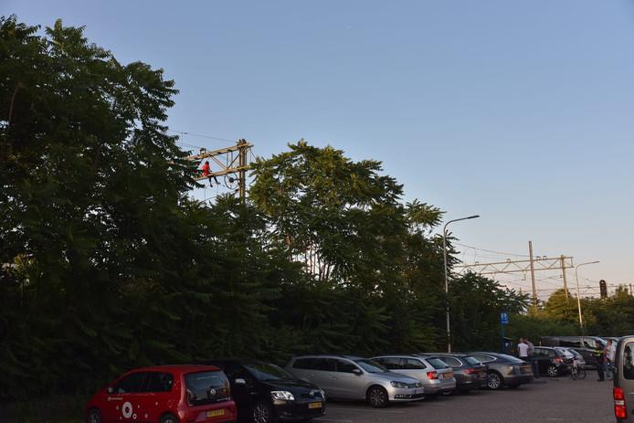 Man klimt in bovenleidingsportaal bij Station Tilburg