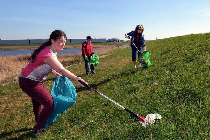 Larissa van Gurchom, Frank Govers en Els Roepers prikken afval aan de Noordlandseweg.