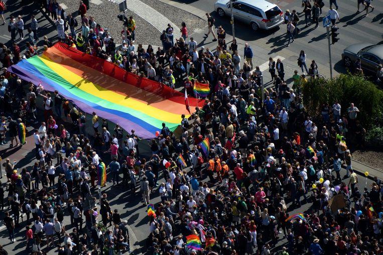 Een menigte met grote regenboogvlag in Warschau Beeld epa
