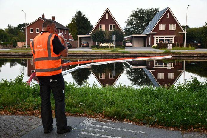 Een medewerker van het Waterschap Vechtstromen langs kanaal Almelo de Haandrik bij Daarlerveen, waar de olie werd gevonden. De schoonmaakwerkzaamheden zijn donderdagochtend afgerond.