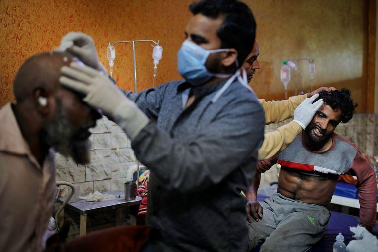 Medici verzorgen gewonden na rellen in New Delhi, India. De grootste democratie ter wereld is gedegradeerd tot 'gedeeltelijk vrij'. Beeld AP