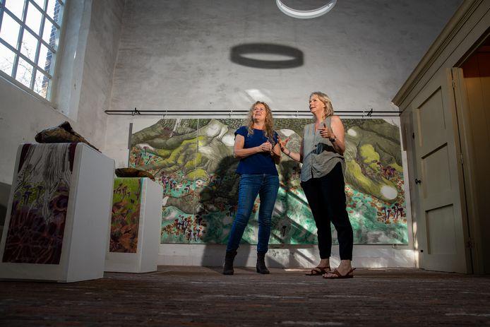 BATENBURG:  Susan Reijnders (links) en Wietske Hellinga voor het grote schilderij van Reijnders van de wortels van de beuk. Links meer schilderwerk van Reijnders en keramiek van Hellinga.