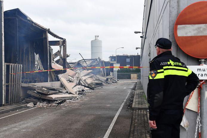 Een agent houdt een oogje in het zeil bij de verwoeste opslagloods in Boxmeer.