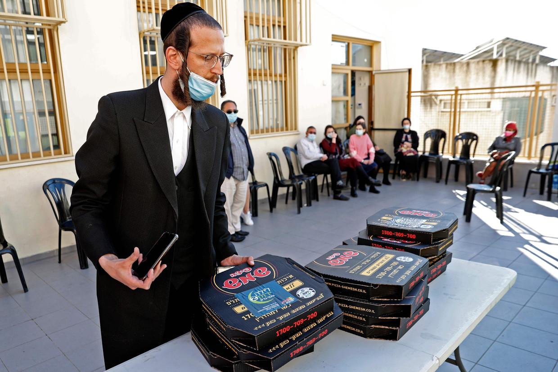 Mensen mogen een pizza meenemen nadat ze zijn ingeënt met het Pfizer-vaccin tegen corona in een gezondheidscentrum in de Israëlische stad Bnei Brak, waar veel orthodoxe Joden wonen.  Beeld Jack Guez / AFP