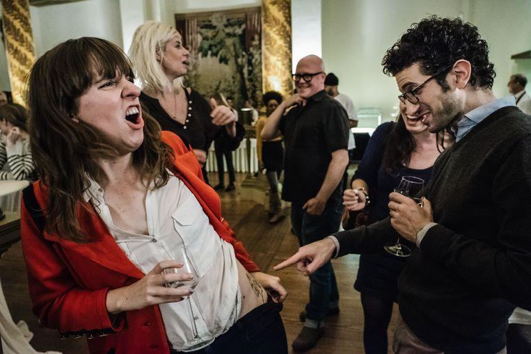 Sarah Vandeursen showt haar tattoo van Paul D'Hoore. Marnix Peeters (m.) lacht mee op de achtergrond. Beeld Wouter Van Vooren