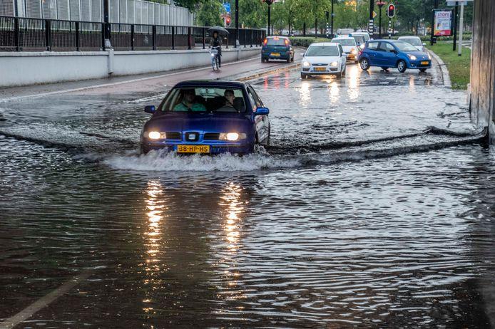 Auto's waden onder het spoorviaduct van Heuvelring en NS Plein door het water.