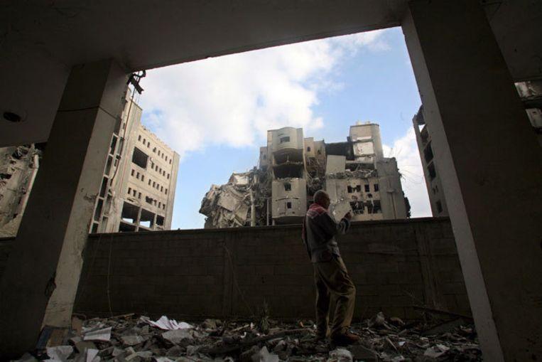 Een Palestijn inspecteert de schade aan zijn huis. Bij het Israëlische luchtoffensief zijn tot nu toe zeker 370 Palestijnen omgekomen. Foto EPA/Mohammed Saber Beeld