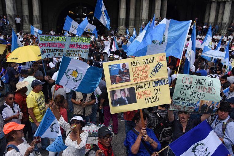 Betogers demonstreren in het centrum van Guatemala-Stad tegen president Jimmy Morales. Een vrouw houdt een bord omhoog waarop naast een foto van Morales onder meer te lezen valt: 'Vriend van criminelen, vijand van het volk'.