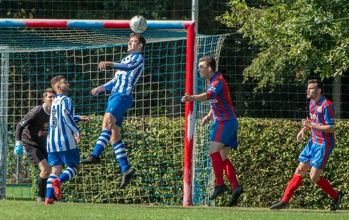 De Zwaluw-doelman Koen Minten kijkt toe hoe teamgenoot Stijn Caspers de bal weghaalt tegen Heijen.