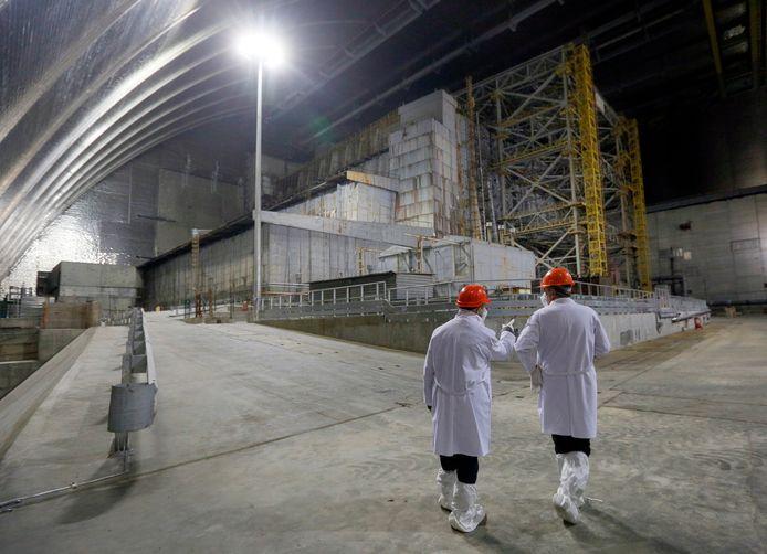 Onderzoekers wandelen langs het omhulsel over de ontplofte kernreactor.