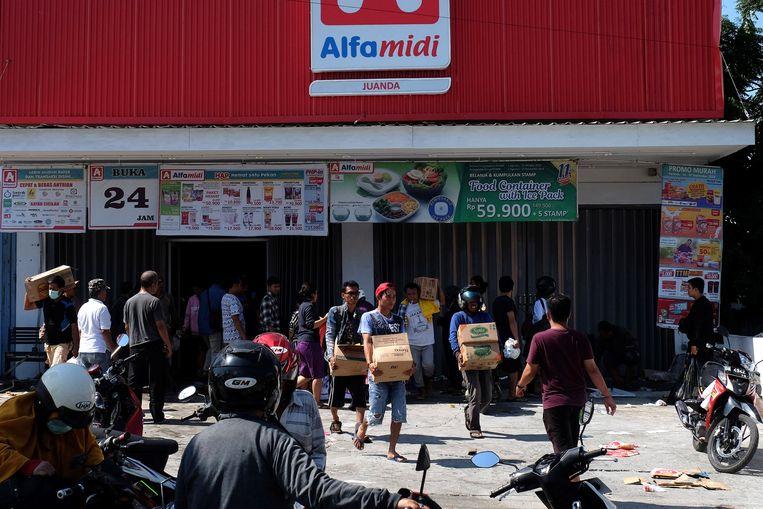 Mensen plunderen winkels in Palu. De overheid staat het voorlopig toe.
