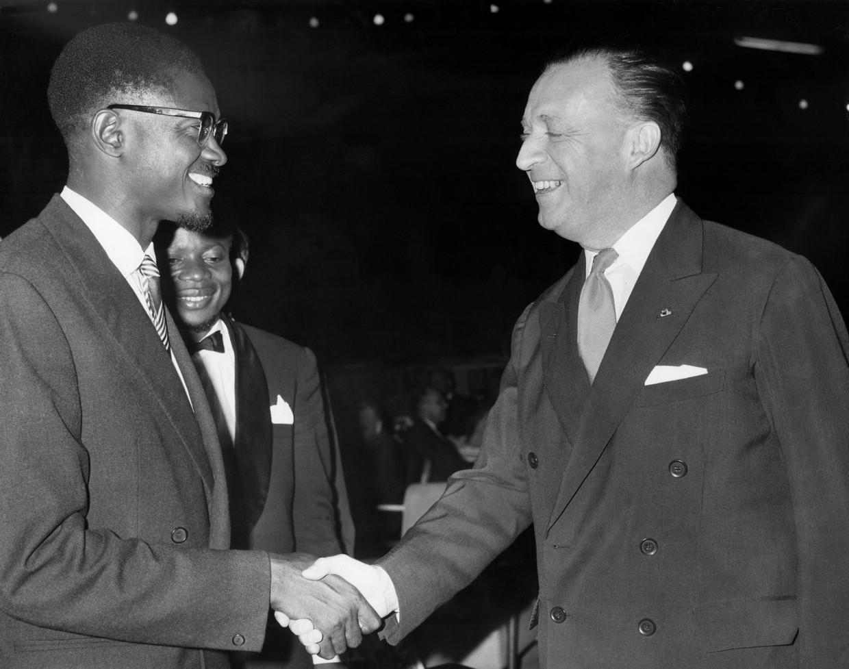 Patrice Lumumba, de eerste Congolese premier, schudt de hand van de Belgische ambassadeur Jean van den Bosch op 4 juli 1960. In september werd Lumumba afgezet, in januari 1961 werd hij vermoord. Beeld AP