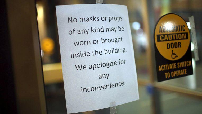 Waarschuwing op de deur van een gebouw niet ver van de plek waar de schietpartij gisteren plaatsvond. Maskers of verkleedkleren zijn verboden. Beeld getty