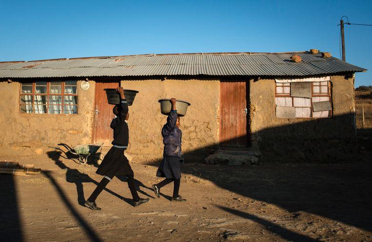 Twee schoolmeisjes dragen water naar hun klaslokaal in Amajuba, Kwazulu-Natal. Beeld Bram Lammers