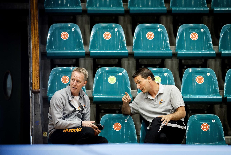 Coach Bram van Bokhoven in gesprek met coach Vincent Wevers (links) tijdens een training van het Nederlands turnteam.