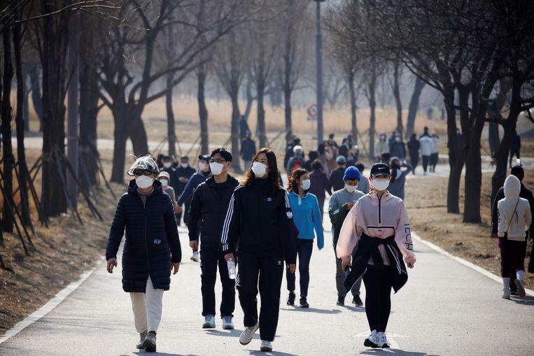 Wandelaars in een park in Seoul. Uit een studie van de World Obesity Federation blijkt dat het overgrote deel van de coronadoden viel in landen waar veel overgewicht voorkomt. Zuid-Korea vormt juist een positief voorbeeld. Beeld REUTERS