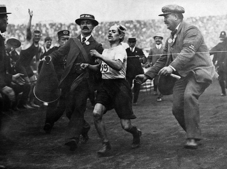 Officials helpen Dorando Pietri in 1908 over de finish, nadat de Italiaan in de finale een paar keren ten val is gekomen.   Beeld Corbis via Getty Images