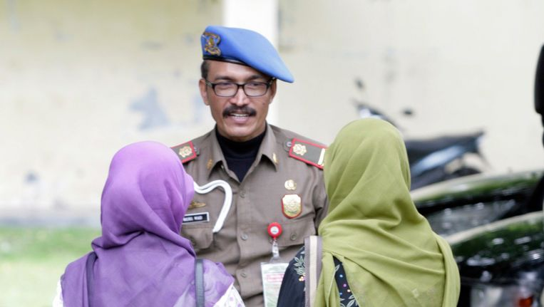 Een agent van de sharian-eenheid praat met twee vrouwen die gearresteerd waren voor het dragen van (te) strakke spijkerbroeken. Beeld EPA