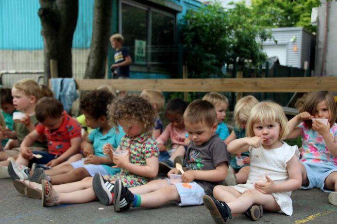 Deze kinderen genieten van hun ijsje op het alternatief schoolfeest.