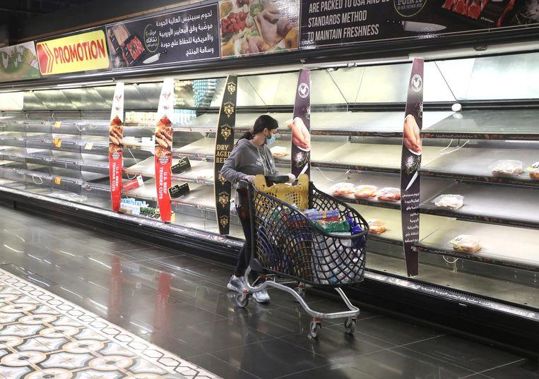 Een vrouw loopt langs de lege schappen in een Libaneze supermarkt. Beeld REUTERS