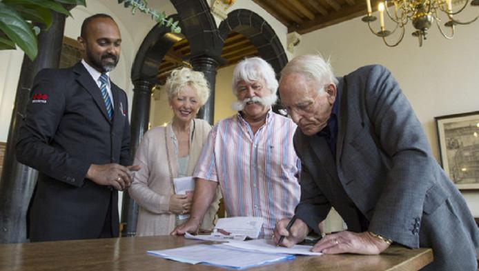 Frans Verbeek (rechts) en Martijn Stoelinga (midden) zetten hun handtekening tegen de komst van een asielzoekerscentrum.