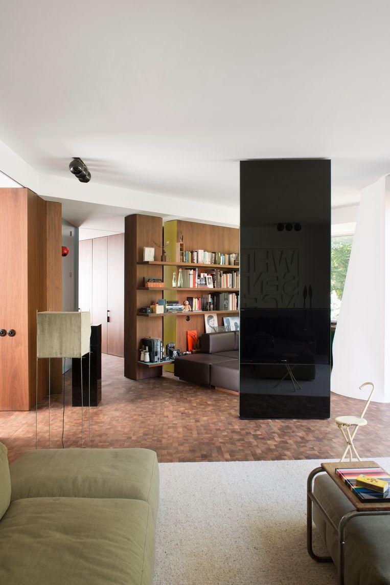 Een spiegelende kolom die eveneens dienstdoet als tv splitst de woonkamer op in twee aparte, maar knusse hoeken. Beeld Verne