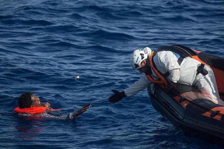Een redder van het Migrant Offsure Aid Station probeert een man aan boord te helpen in de Middellandse Zee. (Archieffoto)