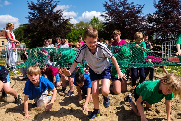 De leerlingen moesten door een zandbak onder een net kruipen.