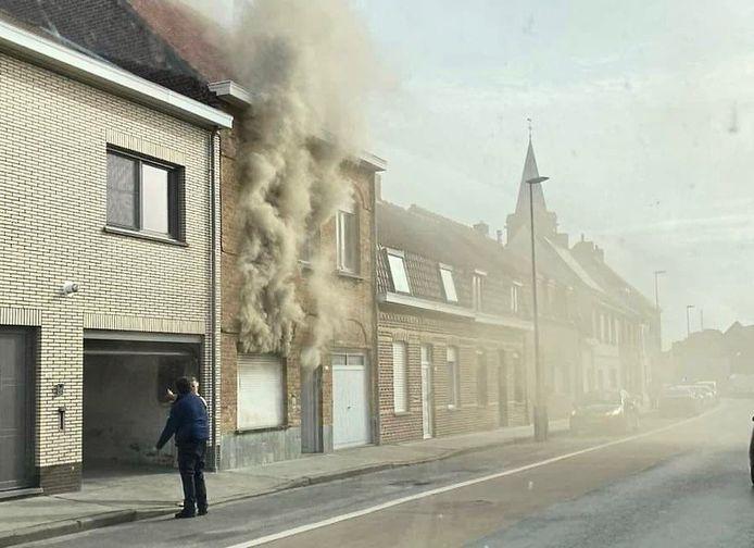 Net voor aankomst van de brandweer ontsnappen dikke rookwolken uit de rijwoning langs de Veurnseweg in Brielen (Ieper).