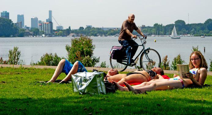 Zonaanbidders genieten van het lekkere weer aan de Kralingse Plas in het Kralingse Bos in Rotterdam.