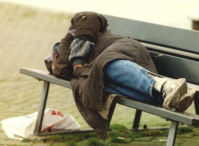 Een dakloze op een bankje.